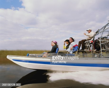 Driver and four passengers on airboat, side view : Stock Photo