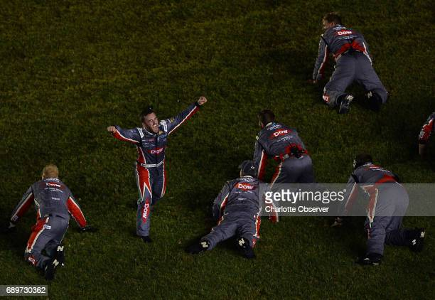 NASCAR driver Austin Dillon leads his team in doing a head first slide into the infield grass as they celebrate winning the CocaCola 600 at Charlotte...