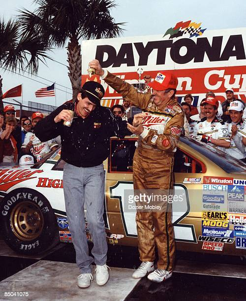 Driver Bobby Allison celebrates in Victory Lane by pouring Miller beer over the head of his son Davey Allison on February 14 1988 after winning the...