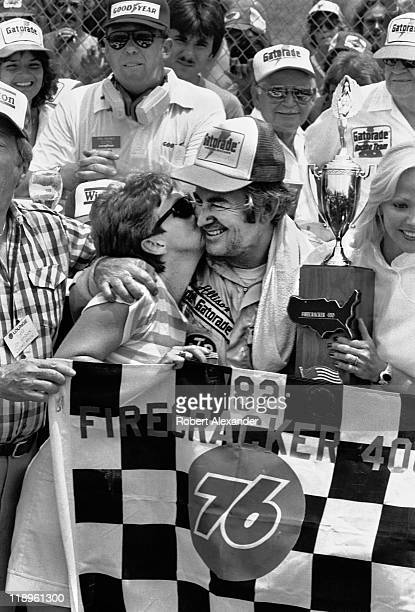 NASCAR driver Bobby Allison gets a kiss on the check from his wife Judy as they celebrate his 1982 Firecracker 400 win in Victory Lane on July 4 1982...