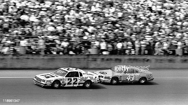 NASCAR driver Bobby Allison leads Richard Petty as they drive past the Daytona International Speedway grandstands during the 1987 Daytona 500 on...
