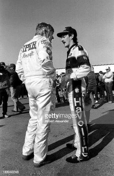 NASCAR driver Bobby Allison left talks with his son fellow race driver Davey Allison in the Daytona International Speedway garage prior to the 1988...