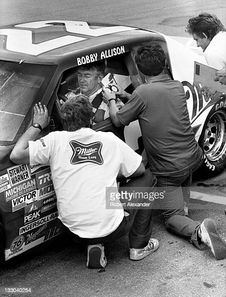 NASCAR driver Bobby Allison talks with his crew members during a practice session for the 1985 Firecracker 400 on July 3 1985 at the Daytona...