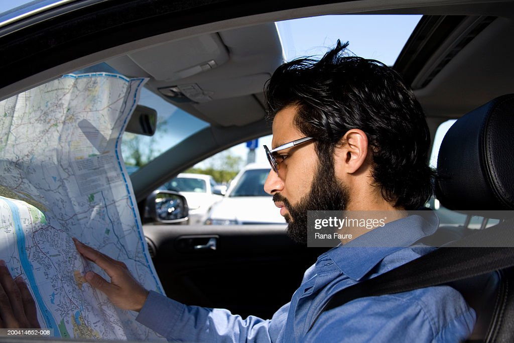 Driver checking route on road map, side view : Stock Photo