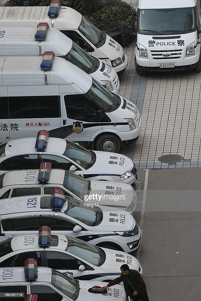 A driver cleans the police car outside Guiyang Intermediate People's Court on January 27, 2013 in Guiyang, China. The trial of Bo Xilai, former party chief of Chongqing will open in Guiyang Intermediate People's Court on January 28, Hong Kong's newspaper Ta Kung Pao reports.