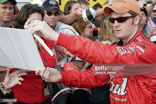 Driver Dale Earnhardt Jr gives his fans his autograph at Pocono Raceway prior to the Pocono 500 Qualifying Round at Pocono Raceway Long Pond...