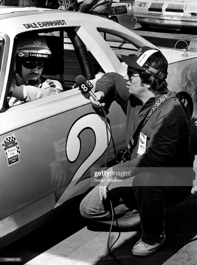 NASCAR driver Dale Earnhardt Sr is interviewed by a TV reporter as he sits in his car at the Daytona International Speedway prior to the start of the...