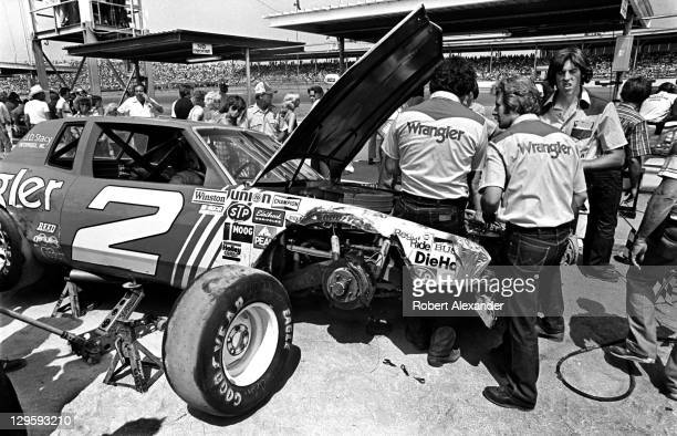 NASCAR driver Dale Earnhardt Sr sits in his race car as crew members make repairs after an accident during the 1981 Firecracker 400 on July 4 1981 at...