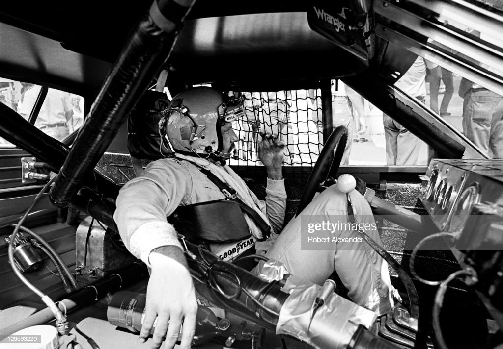 NASCAR driver Dale Earnhardt Sr sits in his race car while it is repaired after an accident during the 1981 Firecracker 400 on July 4 1981 at the...