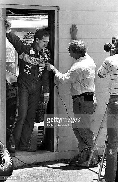 NASCAR driver Dale Earnhardt Sr talks with a television reporter prior to the start of the 1985 Firecracker 400 on July 4 1985 at the Daytona...