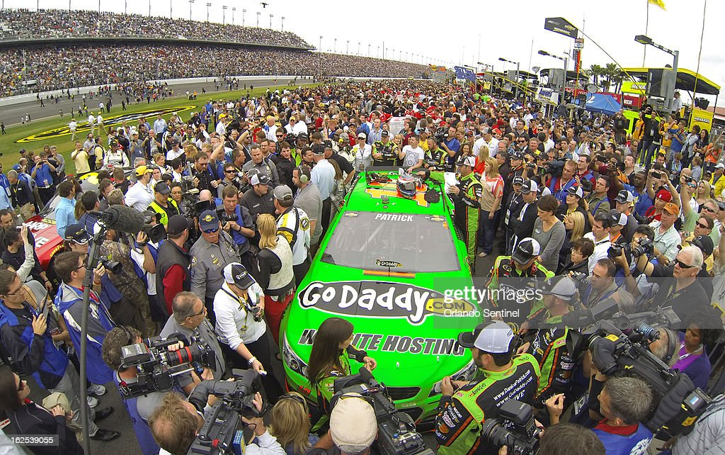 Driver Danica Patrick stands at the front of her car, as a crowd of race officials, fans and media jam pit row around her Chevrolet before the start of the Daytona 500 at Daytona International Speedway in Daytona Beach, Florida, Sunday, February 24, 2013.