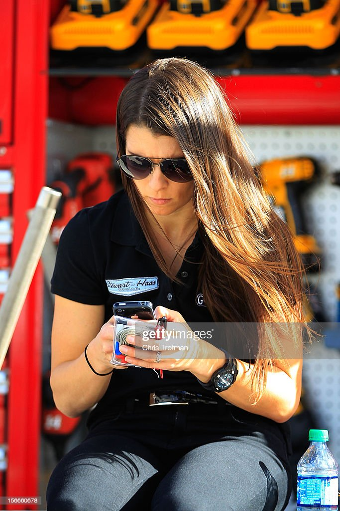 Driver Danica Patrick uses her Smartphone as she sits on pit road wall prior to the NASCAR Sprint Cup Series Ford EcoBoost 400 at Homestead-Miami Speedway on November 18, 2012 in Homestead, Florida.