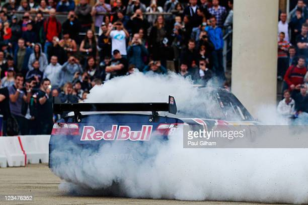 F1 driver Daniel Ricciardo of Australia performs donuts for the crowd in the Red Bull NASCAR car after driving through the city streets during the...