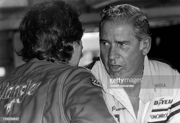 NASCAR driver David Pearson right talks with fellow race car driver Dale Earnhardt Sr in the Daytona International Speedway garage prior to the start...