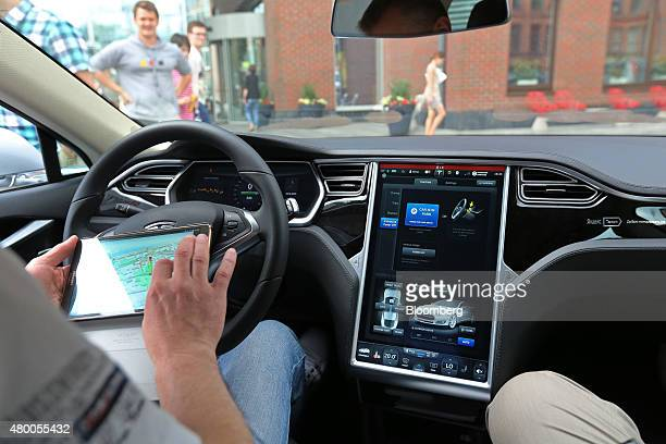 A driver demonstrates the operation of a digital control system inside a Tesla electric vehicle manufactured by Tesla Motors Inc during a...