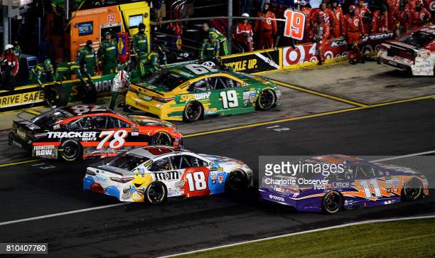 NASCAR driver Denny Hamlin right and Kyle Busch center beat Martin Truex Jr left off pit road at Charlotte Motor Speedway during the third segment of...