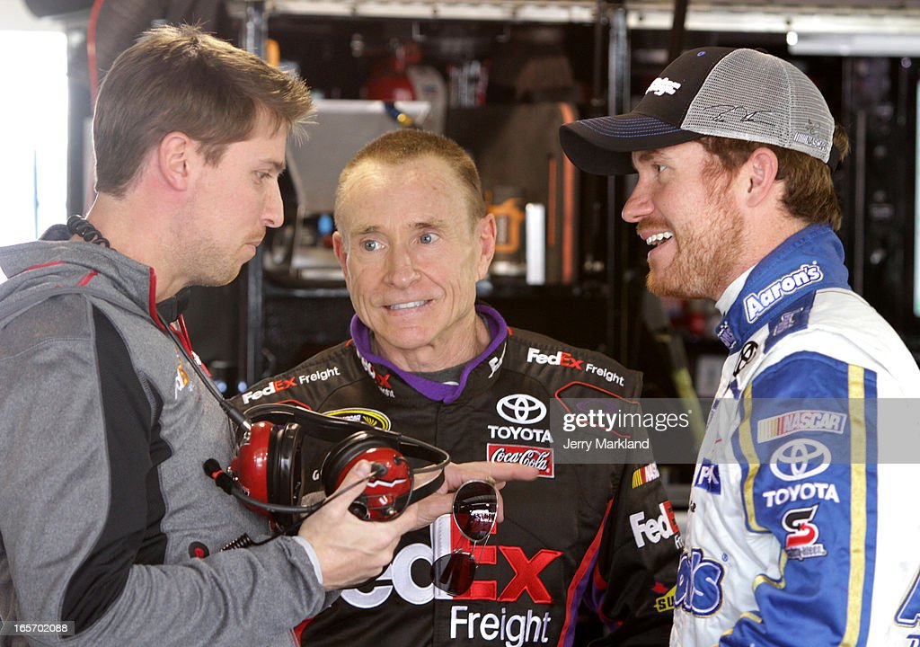 Driver Denny Hamlin talks to Mark Martin, driver of the #11 FedEx Freight Toyota, and Brian Vickers, driver of the #55 Jet Edge Toyota, during practice for the NASCAR Sprint Cup Series STP Gas Booster 500 on April 5, 2013 at Martinsville Speedway in Ridgeway, Virginia.