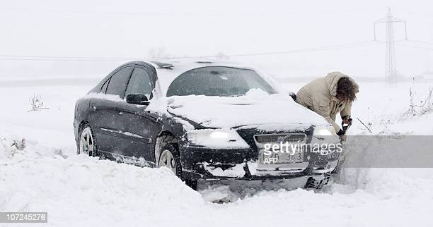 A driver digs her car out of snow on the road between Trelleborg and Malmo after heavy snowfall on December 2 2010 Fresh snowfalls swept northern...