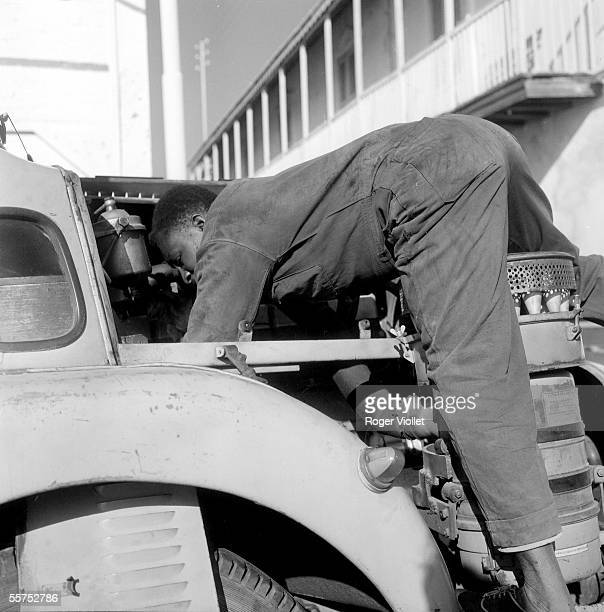 Driver examining the engine of his lorry Saint Louis in January 1963 RV251132