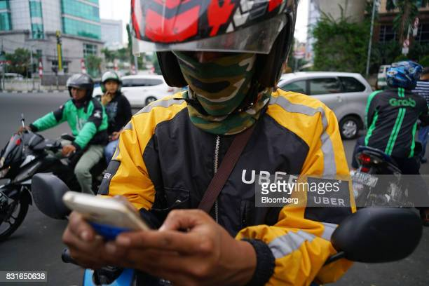 A driver for Uber Technologies Inc's UberMotor service center uses his smartphone while a GrabBike motorcycle driver right stands by as a GoJek...