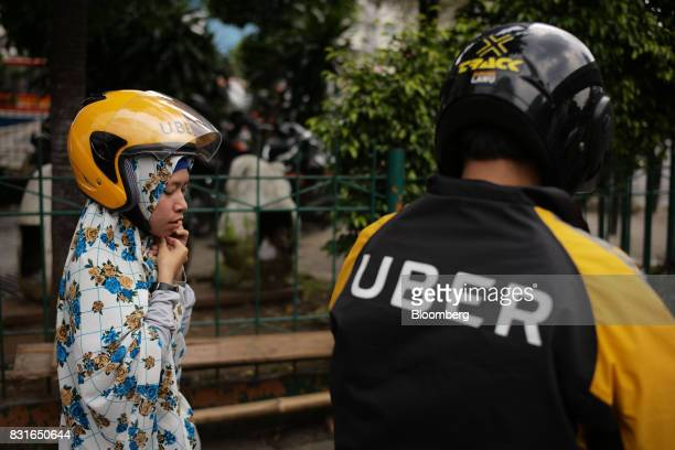 A driver for Uber Technologies Inc's UberMotor service right looks on as his passenger secures her helmet in Jakarta Indonesia on Sunday Aug 13 2017...
