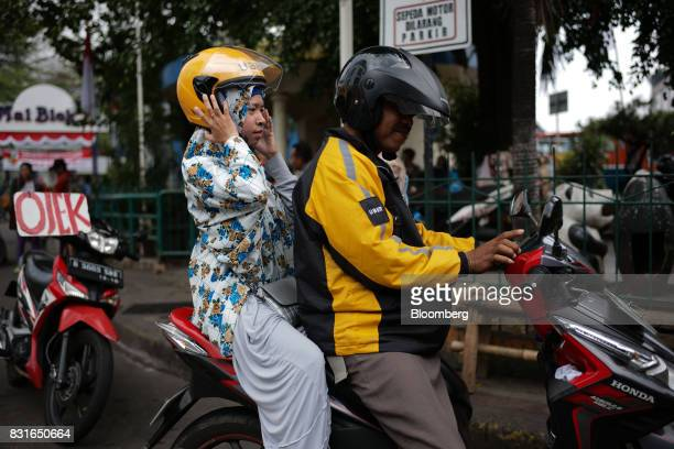A driver for Uber Technologies Inc's UberMotor service right waits as his passenger adjusts her helmet in Jakarta Indonesia on Sunday Aug 13 2017...