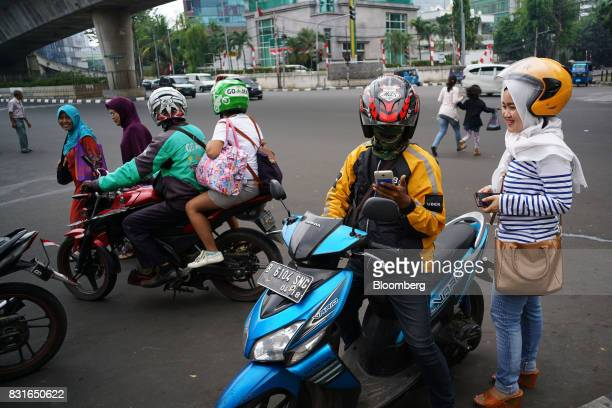A driver for Uber Technologies Inc's UberMotor service second right collects a passenger while a GoJek motorcycle driver left and passenger prepare...