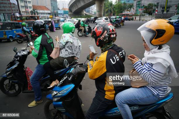 A driver for Uber Technologies Inc's UberMotor service second right and a GoJek motorcycle driver left collect their passengers in Jakarta Indonesia...