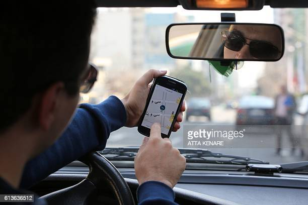 A driver from the startup company Snapp which offers a taxi service app checks the app on his mobile in Tehran on October 4 2016 Tehran already has...