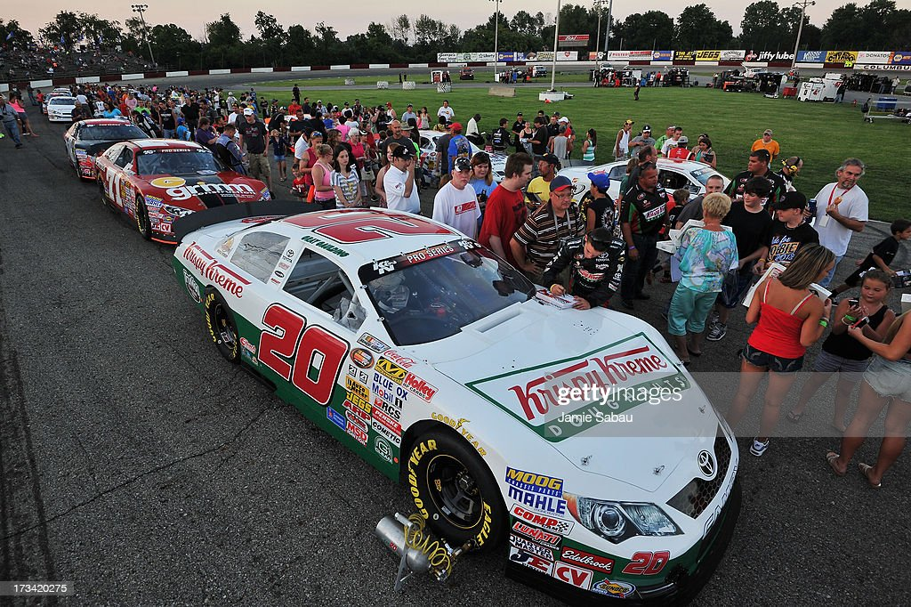 Driver Gray Gaulding signs autographs for young fans before the start of the NASCAR K&N Pro Series, East NAPA 150 on July 13, 2013 at Columbus Motor Speedway in Columbus, Ohio.