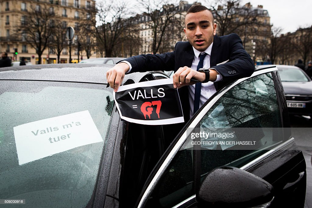 A VTC driver hold a sign that reads, 'Valls=G7' refering to French Prime Minister Manuel Valls and the G7 taxi company, as VTC vehicles block the roundabout at Place de la Nations to protest against the LOTI law in Paris, on February 9, 2016. Uber and other ride-hailing companies, known in France as 'voitures de tourisme avec chauffeur' (VTC) are a class of companies that allow passengers to book rides with independent professional chauffeurs. / AFP / Geoffroy Van der Hasselt