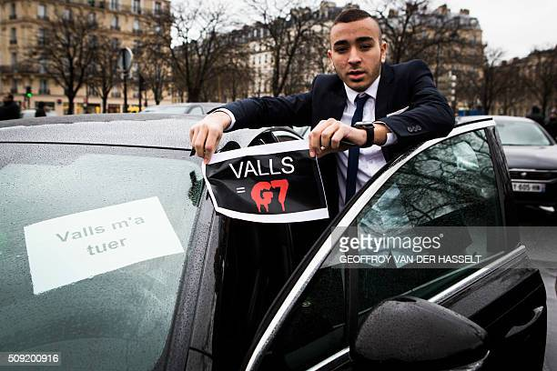 A VTC driver hold a sign that reads 'Valls=G7' refering to French Prime Minister Manuel Valls and the G7 taxi company as VTC vehicles block the...