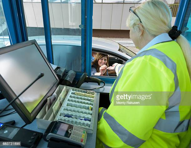 Driver in car paying toll booth at bridge