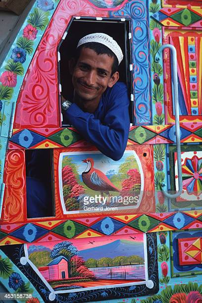 A driver in the cab of a hand painted truck in Karachi