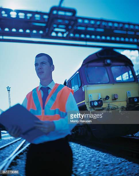 Driver Inspector Stands on Railway Sidings With a Freight Train Behind him, Immingham, Humberside, UK