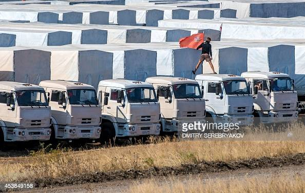 A driver installs a red flag on his lorry parked with other lorries of the Russian humanitarian convoy not far from a checkpoint at the Ukrainian...