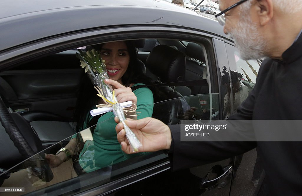 A driver is offered a flower by a cleric during a gathering of Clerics representing the various Lebanese religious communities for peace in central Beirut on the eve of the anniversary of the 1975-1990 civil war on April 12, 2013.