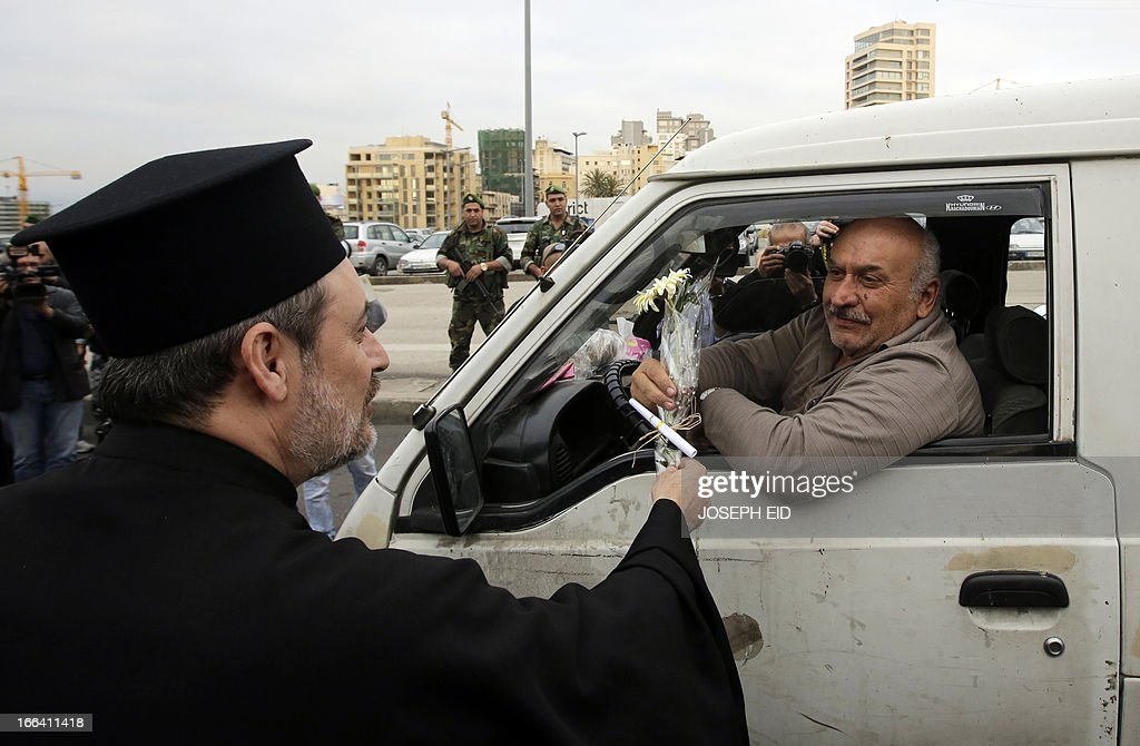 A driver is offered a flower by a cleric during a gathering of clerics representing the various Lebanese religious communities for peace in central Beirut on the eve of the anniversary of the 1975-1990 civil war on April 12, 2013. AFP PHOTO/JOSEPH EID