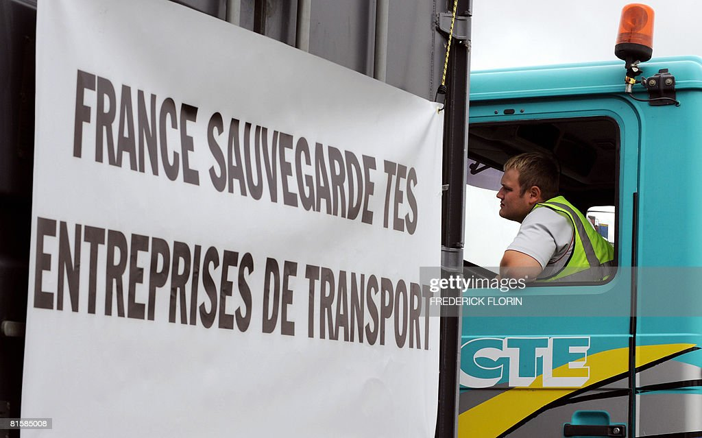 A driver is pictured as go-slow road convoys drivers prepare to disrupt traffic on June 16, 2008 in Selestat, eastern France, to ask for measures to counter soaring fuel prices. The protests follows on similar action staged by fishermen and farmers since early May. The front banner reads : 'France save your transport companies'.