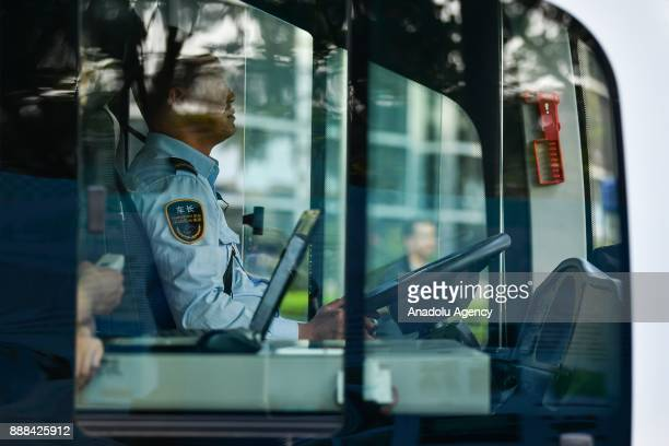 Driver is seen in the selfdriving bus when it runs on a road on December 8 2017 in Shenzhen China The buses have designed speed of 10 to 30 kph...