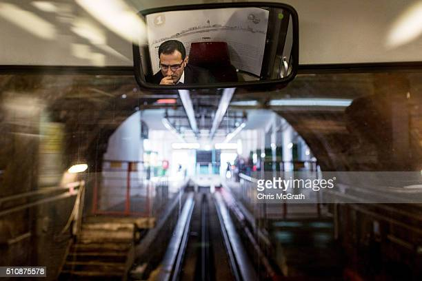 A driver is seen reflected in the rear vision mirror of The Tunel underground railway as it pulls into the Istiklal street station on February 17...