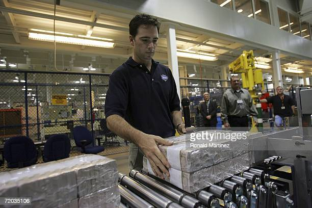 NASCAR driver Jimmie Johnson moves bricks of US currency each worth $200000 down a conveyor belt during a production tour at the Bureau of Engraving...