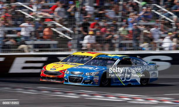 NASCAR driver Jimmie Johnson passes Joey Logano background with 16 laps to go during the O'Reilly Auto Parts 500 on Sunday April 9 2017 at Texas...