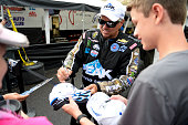 Driver John Force signs autographs for fans during a rain delay at day one of the MoPar Mile High Nationals at Bandimere Speedway on July 22 2016