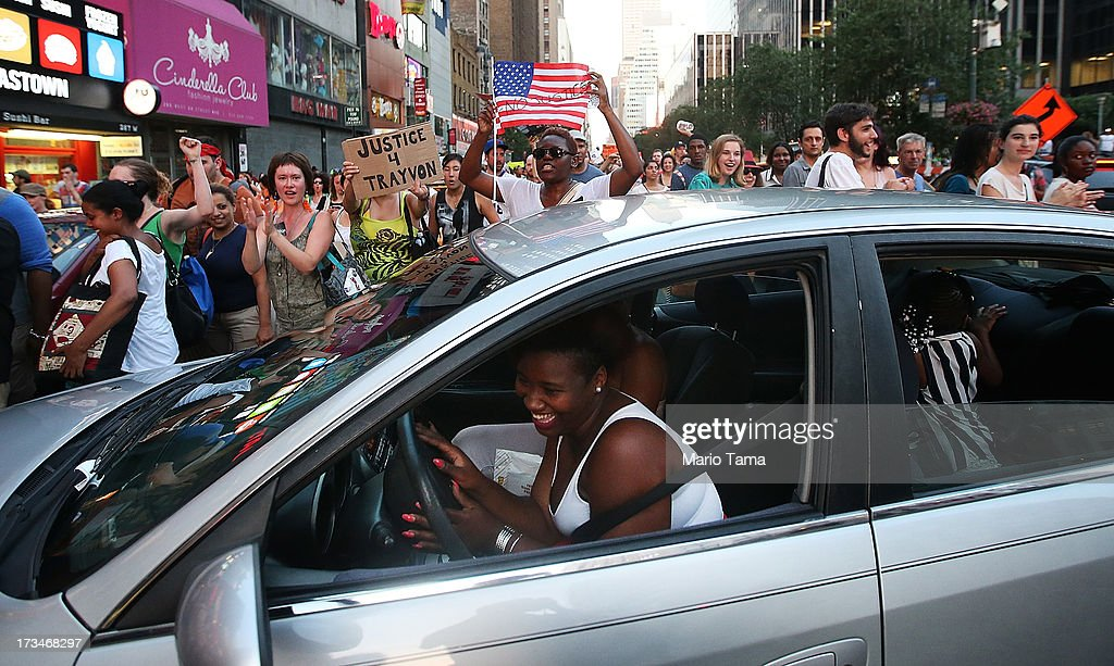 A driver laughs as Trayvon Martin supporters march through the streets of Manhattan blocking her vehicle and other traffic after a rally for Martin in Union Square on July 14, 2013 in New York City. George Zimmerman was acquitted of all charges in the shooting death of Martin July 13 and many protesters questioned the verdict.