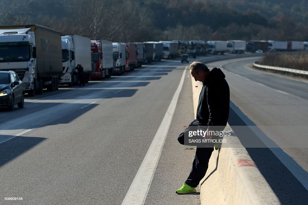 A driver leans against a centre divider to smoke a cigarette as trucks are blocked 2 kilometres from the border crossing of Promachonas between Greece and Bulgaria, in northern Greece, as farmers set up a blockade at customs offices, shutting down the movement of trucks to and from Bulgaria on February 7, 2016. Greek farmers protesting against pension reforms heightened highway and border protests around the country, piling pressure on the leftist government of Prime Minister Alexis Tsipras. The mobilisation which began in mid-January has created tractor blockades at dozens of highway locations and key border crossings to Bulgaria and Turkey, which the farmers intermittently open for a few hours each day. / AFP / SAKIS MITROLIDIS