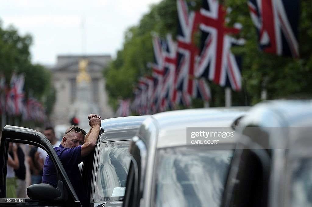 A driver leans on his taxi during a protest by London black cab drivers during a protest against a new private taxi service 'Uber', a mobile phone app, in central London on June 11, 2014. Taxi drivers brought parts of London, Paris and other European cities to a standstill on June 11 as they protested against new private cab apps such as Uber which have shaken up the industry. Thousands of London's iconic black cabs, many of them beeping their horns, filled the roads around Buckingham Palace, Trafalgar Square and the Houses of Parliament to the exclusion of any other vehicles.