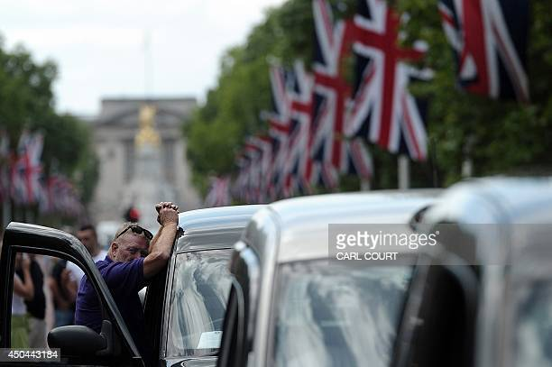 A driver leans on his taxi during a protest by London Black Cab drivers during a protest against a new private taxi service 'Uber' a mobile phone app...