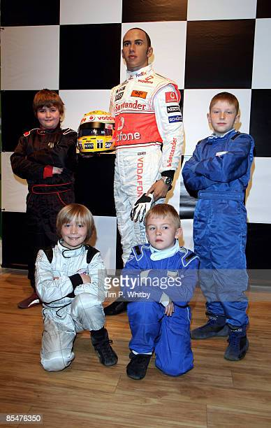 Driver Lewis Hamilton has his waxwork unveiled at Madame Tussauds and appears with F1 champs of the future Archie Tillett Billy Monger Myles Apps and...
