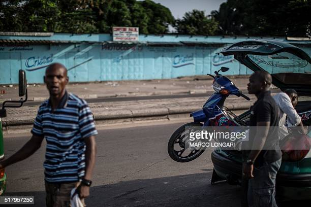 A driver loads a scooter on his taxi as shops are shut down for a 'dead city' strike called by five defeated opposition candidates to protest the...